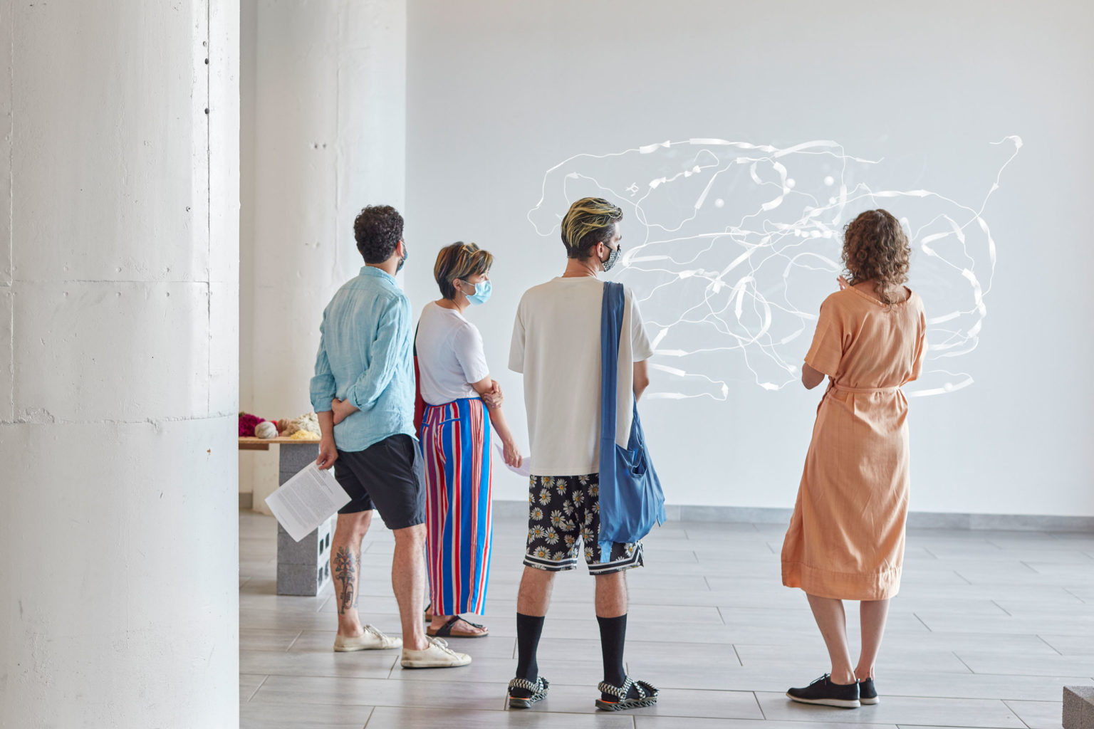 picture of people standing in a museum looking at an exhibit of white lines on a grey wall.