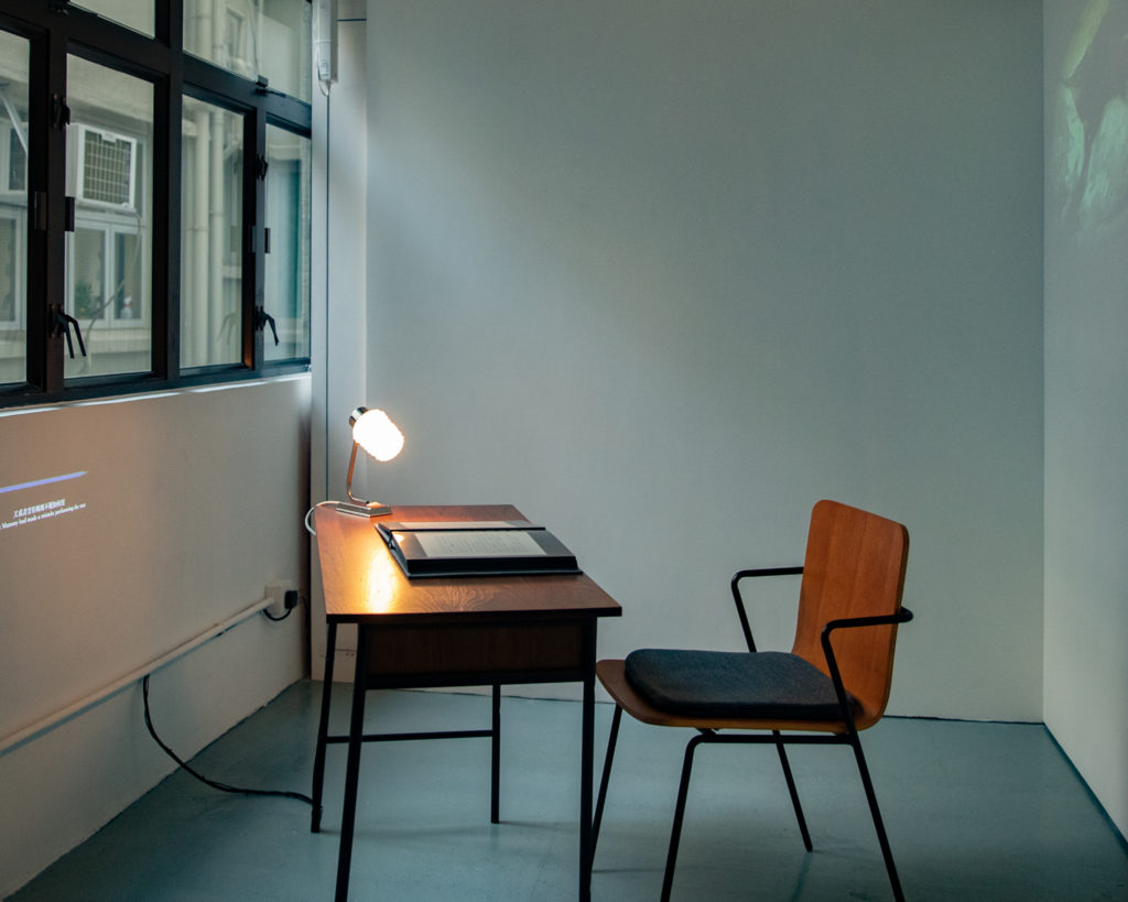photo of lit lamp on a desk in front of a chair