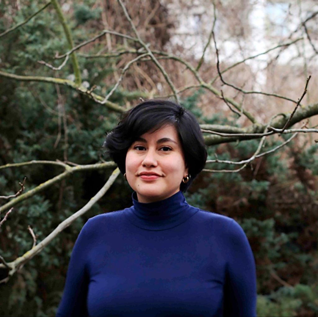 picture of young female with short black hair, gold hoop earrings and blue turtleneck sweater
