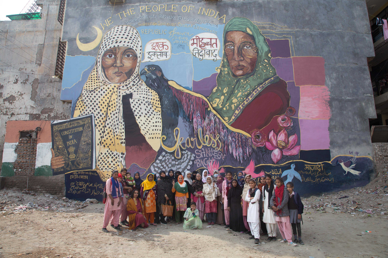 a group of women standing in front of a painted wall mural depicting two women talking