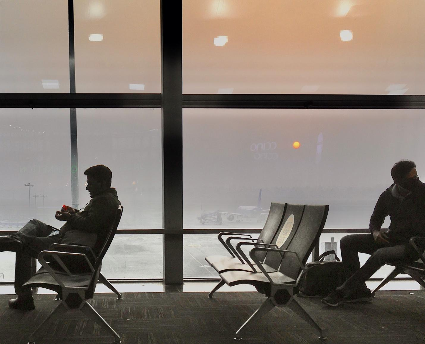 Image of people waiting at an airport, sitting socially distanced